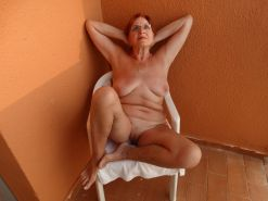 Naked redhead GILF soaking up the sun